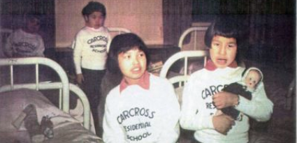 Photograph of children standing beside beds wearing t-shirts that read 'Carcross Residential School'.